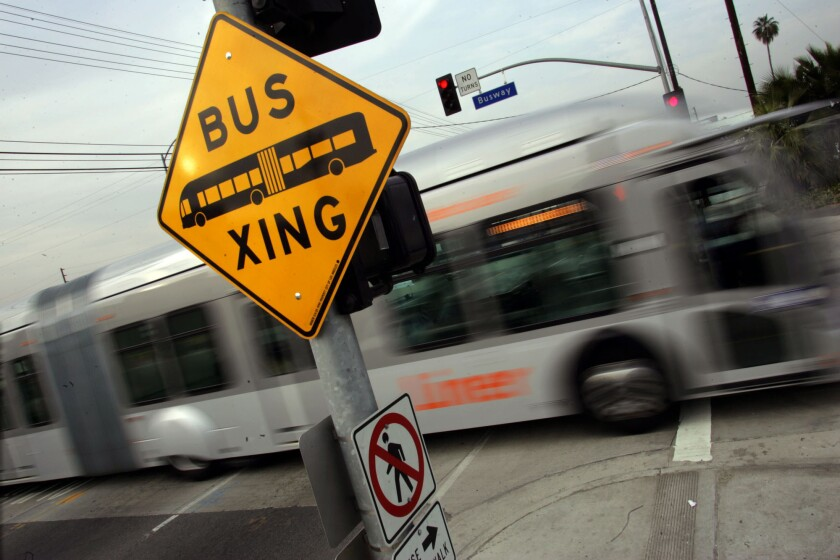 A Metro Orange Line bus travels across Kester Avenue in the San Fernando Valley. A new report says converting the busway to light-rail could cost as much as $1.7 billion.