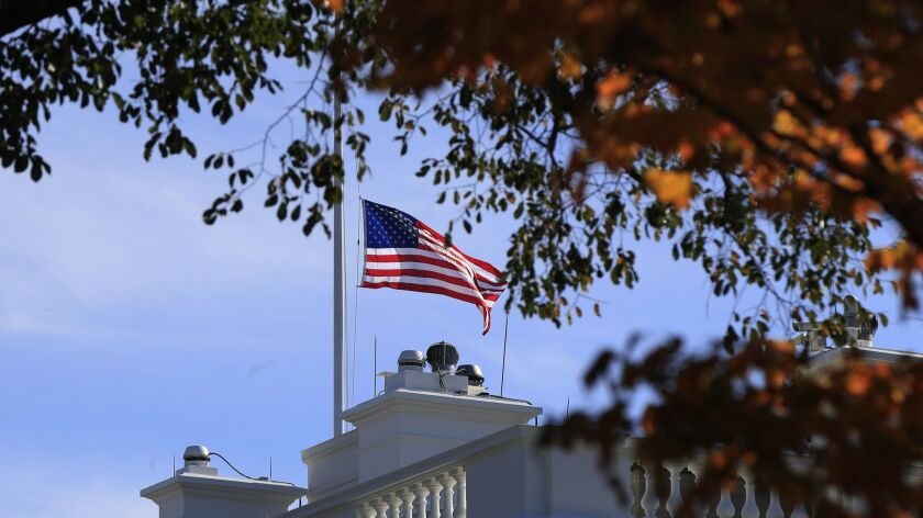 The American flag is lowered at half-staff at the White House in Washington, Thursday, Nov. 8, 2018, to honor the victims of the shooting at a bar in Thousand Oaks, Calif.