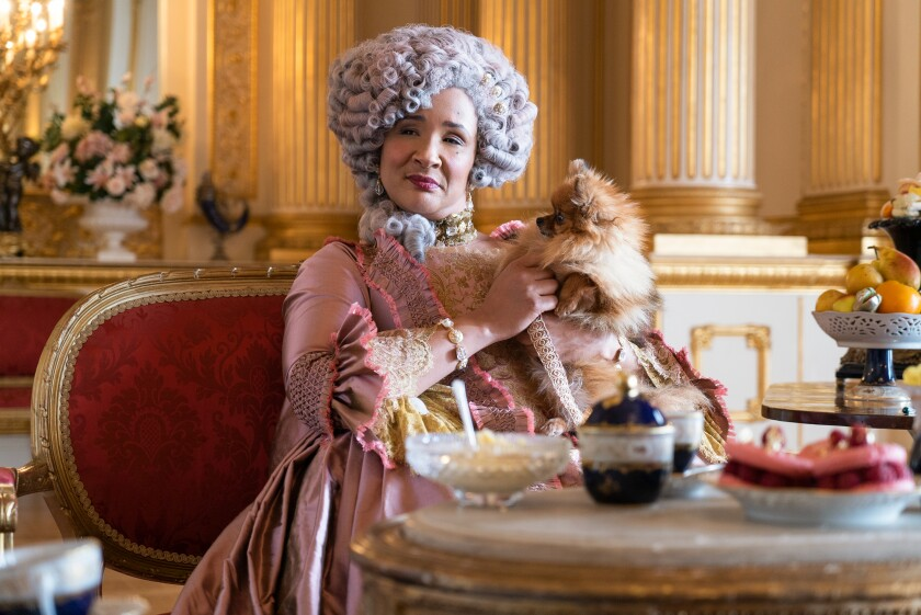 A woman holds a small dog while wearing a tall wig and period gown