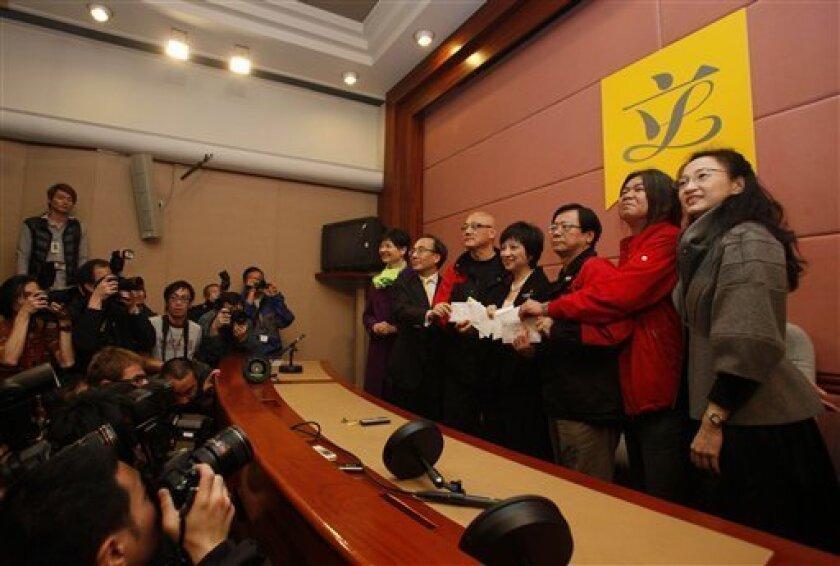 Five Hong Kong legislators Tanya Chan, right, Leung Kwok-hung, second right, Wong Yuk-man, third right, Albert Chan, third left, Alan Leong, second left, present the resignation letter to Pauline Ng, center, Secretary General inside the Legislative Council in Hong Kong Tuesday, Jan. 26, 2010. The f
