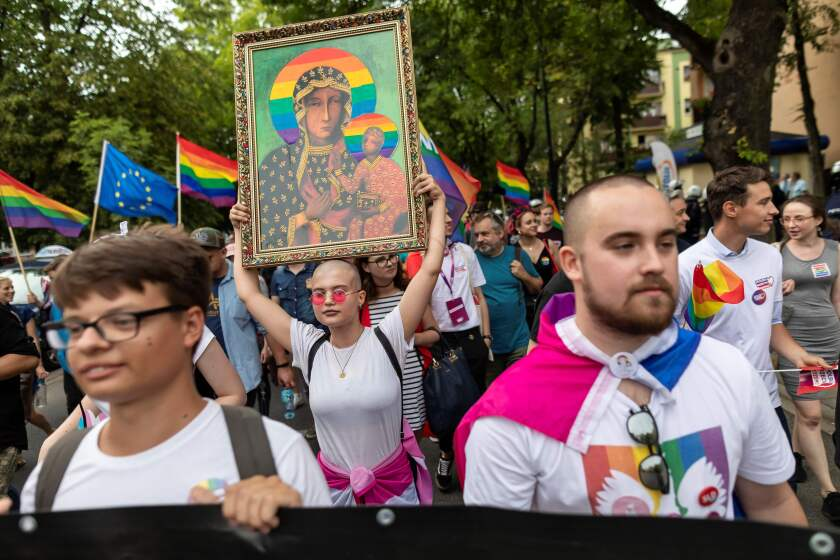 A demonstrator holds a picture depicting the Virgin Mary with a rainbow halo during a pride gathering in August in central Poland.