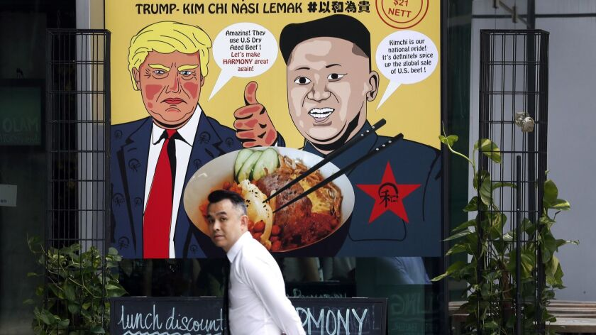 A man walks past an advertisement board of cartoon caricatures of U.S. President Donald Trump and No