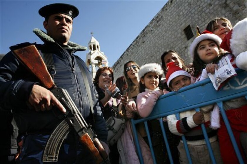 In this Dec. 24, 2007 file photo a Palestinian security force officer stands guard as Christians gather outside the Church of the Nativity, traditionally believed by many to be the birthplace of Jesus Christ, in Manger Square during Christmas festivities in the West Bank town of Bethlehem. After eight bleak years, Jesus' birthplace finally has a Christmas season to cheer about. Tourism blossomed in the 1990's, when peace hopes were alive, but was crushed by the outbreak of fighting in 2000. Christmas after Christmas, tourists were scared off by Palestinian violence and Israeli travel restrictions. This year hotels are booked solid through January, Manger Square is bustling with tourists, and Israeli and Palestinian forces are working together to to make things go smoothly. (AP Photo/Kevin Frayer, File)