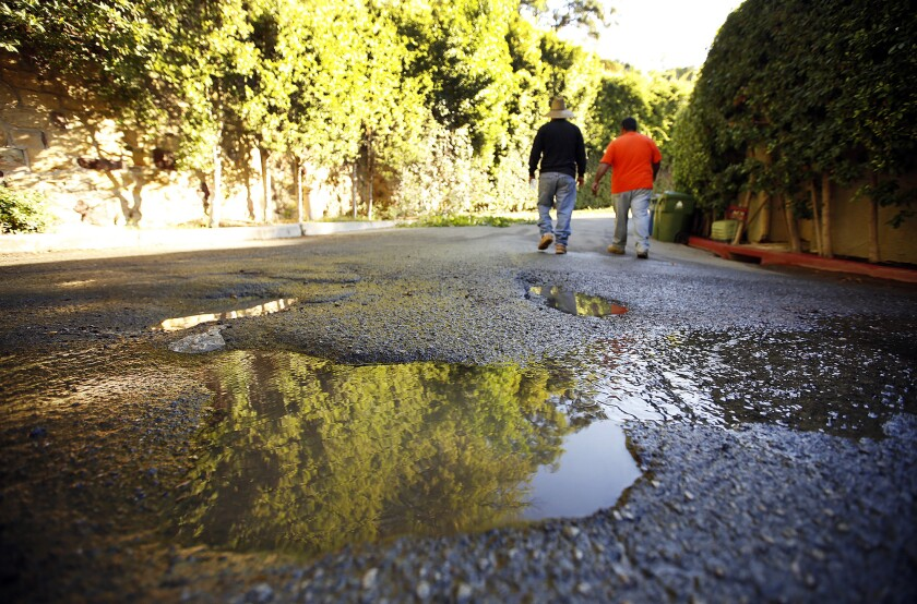 Pot holes fill with running water in the streets surrounding homes in the Bel Air neighborhood of Los Angeles on October 21.