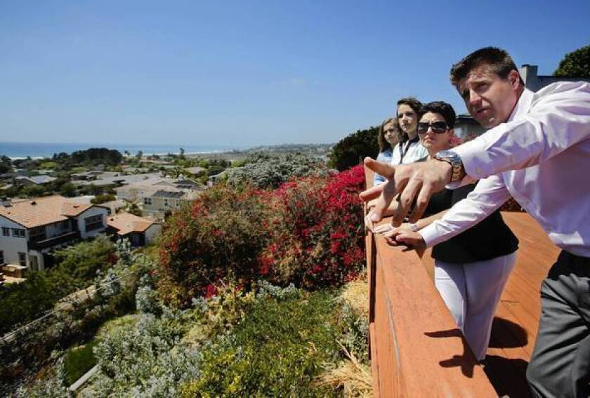 Real estate agent Ryan Mathys, right, talks to the Snyder family about the view from a home in Solana Beach, Calif. The house hadn't been listed for sale, but his client liked the street it was on, so Mathys sent letters, knocked on doors and used social media to find prospective sellers.