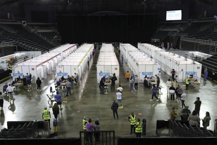 Personas hacen fila en un centro de vacunación montado en la Arena SSE de Belfast, Irlanda del Norte