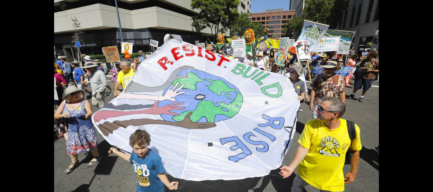 "10-year-old Huxley Smith of La Jolla, center, and his dad, Michael Smith, right, along with others carry a protest banner along the route from San Diego Civic Center Plaza to Embarcadero Marina Park South during the San Diego ""Rise for Climate"" rally and march organized by San Diego 350."