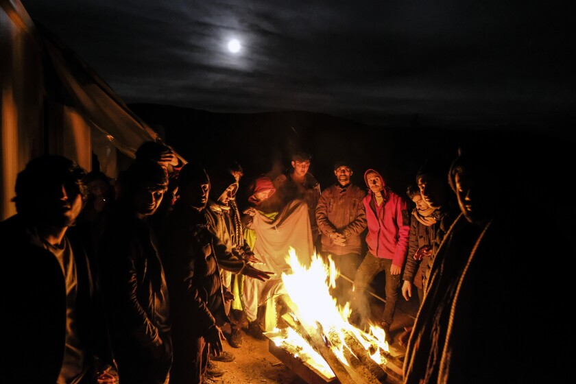 Migrants warm themselves around a fire at the Lipa camp outside Bihac, Bosnia, Wednesday, Dec. 30, 202, after hundreds failed to be relocated from the burnt-out tent camp in the northwest of the country. The migrants were supposed on Tuesday to be transferred from the much-criticized Lipa camp to a new location in the central part of the country, but have instead spent some 24 hours in buses before being told on Wednesday afternoon to disembark and return to the now empty camp site. (AP Photo/Kemal Softic)