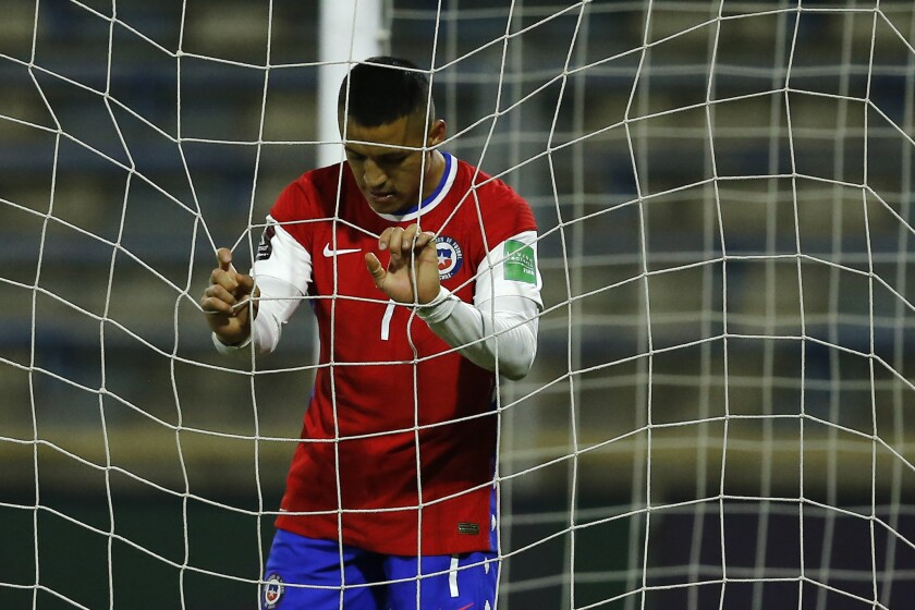 Chile's Alexis Sanchez holds the net during a qualifying soccer match against Bolivia for the FIFA World Cup Qatar 2022 in Santiago, Chile, Wednesday, June 9, 2021. (Marcelo Hernandez, Pool via AP)