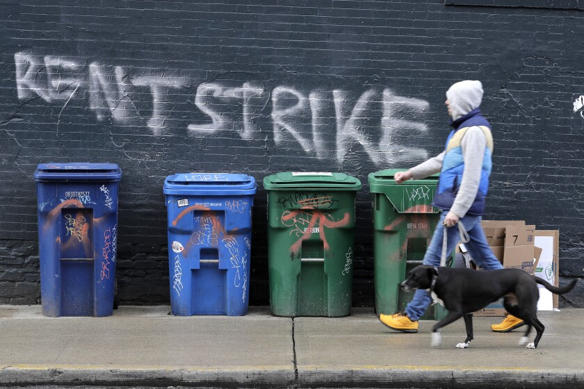"""FILE - In this April 1, 2020, file photo, a pedestrian walks past graffiti that reads """"Rent Strike"""" in Seattle's Capitol Hill neighborhood. The White House announced Tuesday, Sept. 1, that the Centers for Disease Control and Prevention would act under its broad powers to prevent the spread of the coronavirus. The measure would forbid landlords from evicting anyone for failure to pay rent, providing the renter meets criteria. (AP Photo/Ted S. Warren, File)"""