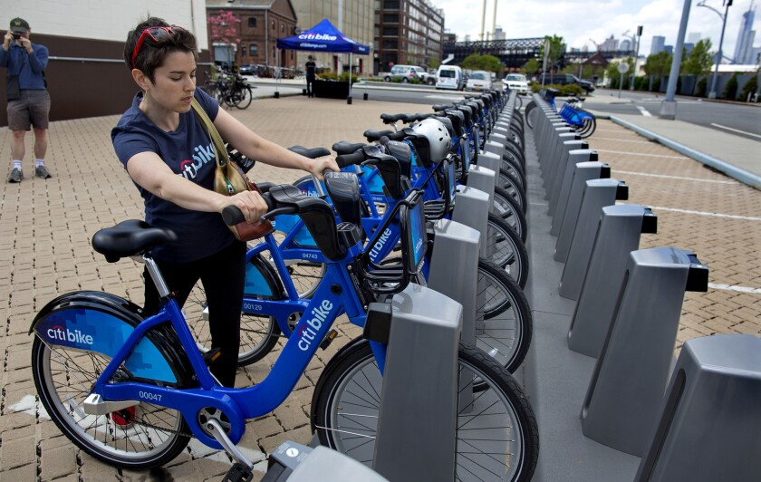 Dani Simons, director of marketing and external affairs with NYC Bike Share, demonstrates the process of returning a bike at a dock and lock station at the Brooklyn Navy Yards.