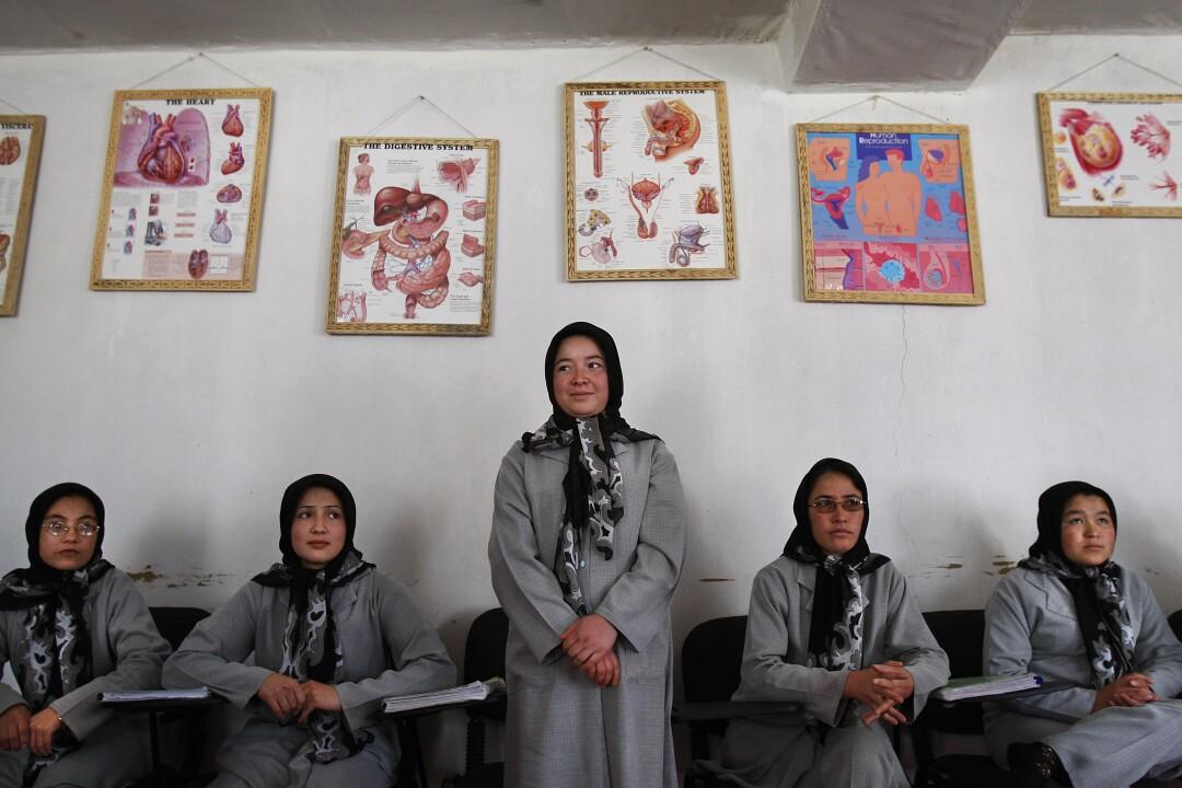 زن جوانی با روسری و لباس خاکستری ایستاده است و چهار زن دیگر دور او نشسته اند