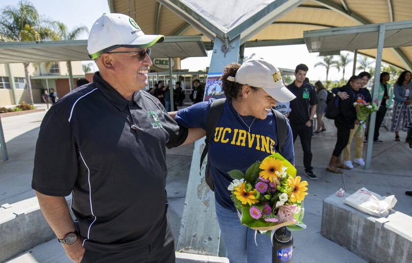 Costa Mesa coach Steve Moreno, left, hugs Tayla Crenshaw during a signing day ceremony on April 25, 2018.