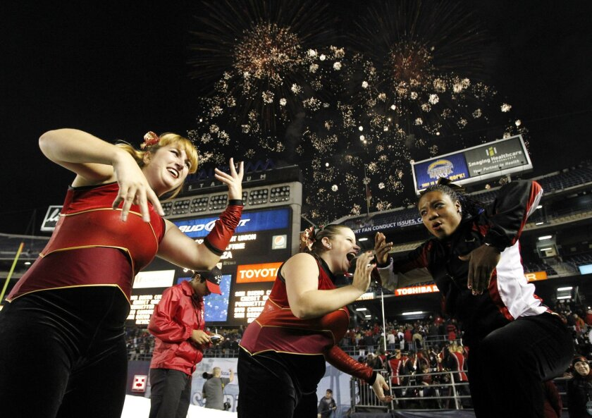 Members of the Aztecs color guard dance as fireworks explode just after they and the Aztecs marching band performed in the San Diego Credit Union Poinsettia Bowl halftime show at Qualcomm Stadium on Thursday.