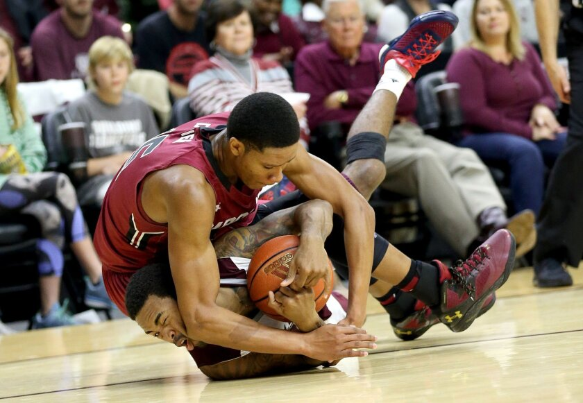 Texas A&M's Anthony Collins (11) fights for a loose ball with South Carolina's PJ Dozier (15) during the first half of an NCAA college basketball game, Saturday, Feb. 6, 2016, in College Station, Texas. (AP Photo/Sam Craft)