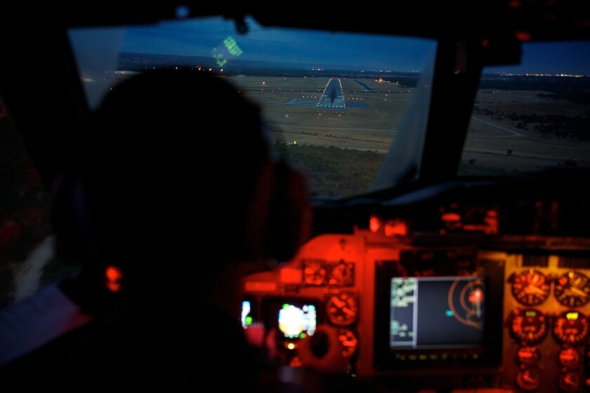 Marc Smith, copilot of an Australian air force AP-3C Orion, approaches the Pearce air base in Perth, Australia. The air and sea search for Malaysia Airlines Flight 370 was suspended Tuesday because of gale-force winds, heavy rain and big waves, the Australian Maritime Safety Authority said.