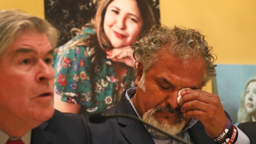 Salvador Albert Corado, father of Melyda Corado, who was shot and killed by LAPD officers at a Trader Joe's in Silver Lake, during a press conference with a family attorney, John Taylor. Melyda's photo is in the background.
