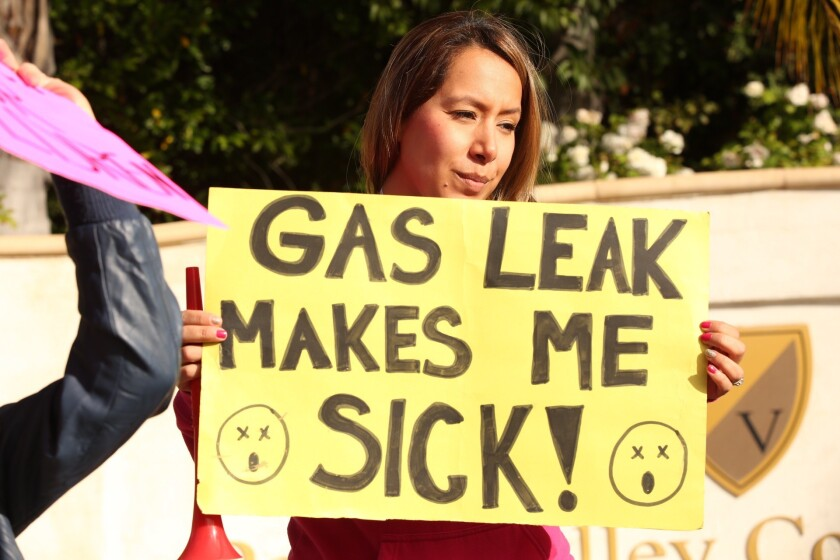 Parent Rocio Arreola holds up a protest sign in Porter Ranch on Dec. 11.