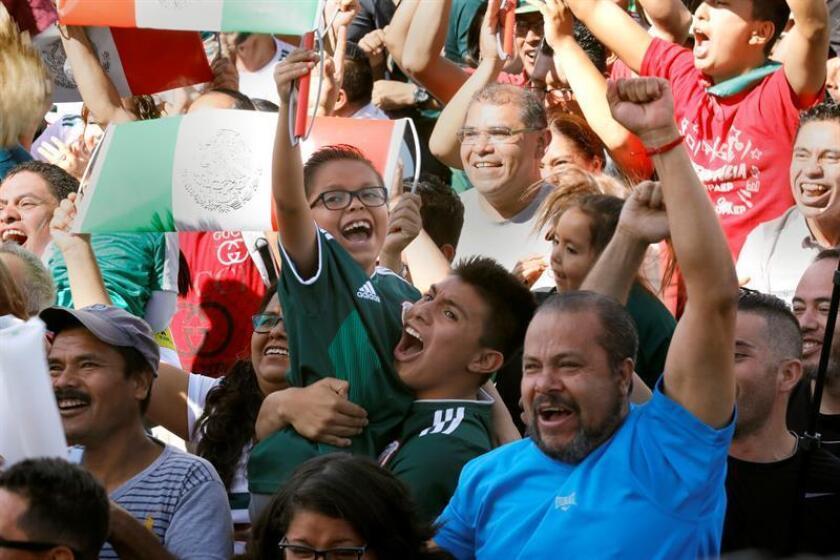 Aficionados celebran el gol de la selección mexicana de fútbol ante Alemania en el Mundial de Rusia, durante una transmisión hoy, domingo 17 de junio de 2018, desde el zócalo de Ciudad de México (México). EFE