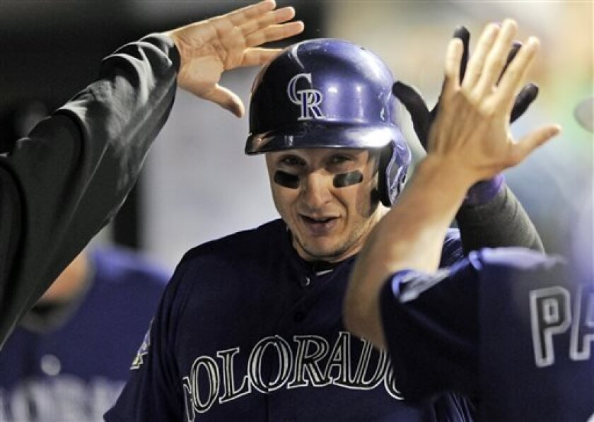 Colorado Rockies' Troy Tulowitzki is congratulated int he dugout by teammates after scoring on an RBI single by Wilin Rosario during the fourth inning of a baseball game against the San Francisco Giants on Tuesday, Aug. 27, 2013, in Denver. (AP Photo/Jack Dempsey)