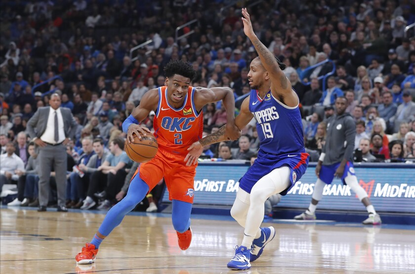 Oklahoma City Thunder guard Shai Gilgeous-Alexander drives around Clippers guard Rodney McGruder.
