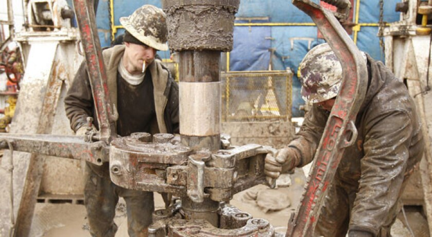 """Rig workers drill a saltwater well to get fluids to be used in hydraulic fracturing, or """"fracking,"""" in Anthony, Kan."""
