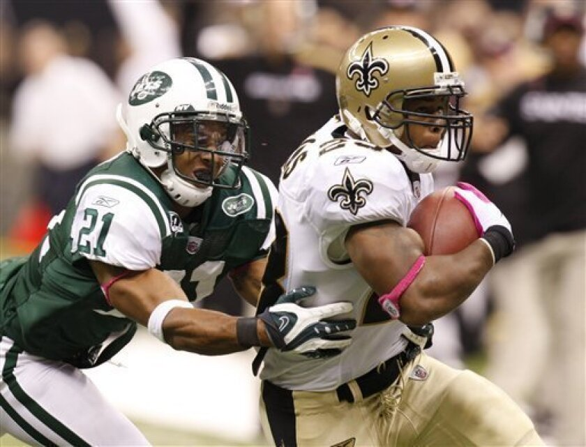 New Orleans Saints running back Pierre Thomas (23) tries to get away from New York Jets cornerback Dwight Lowery (21) in the first half of an NFL football game in New Orleans, Sunday, Oct. 4, 2009. (AP Photo/Bill Haber)