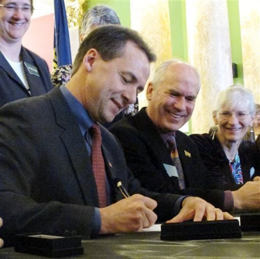 Montana Gov. Steve Bullock, left, state Sen. Tom Facey and advocate Linda Gryczan attend a ceremony signing into law a gay rights bill that has been in the works for two decades on Thursday, April 18, 2013 in Helena, Mont. The measure formally removes an obsolete law, struck down by the courts 16 y