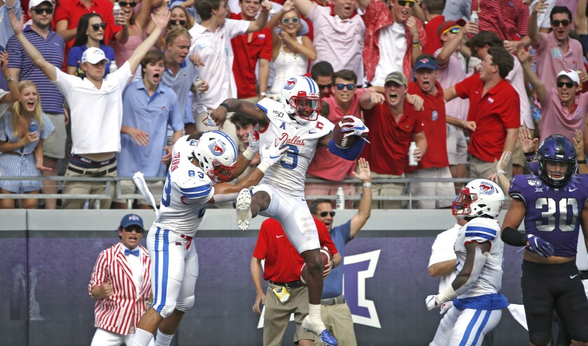 SMU wide receiver James Proche (3) celebrates with teammate and tight end Kylen Granson (83) after catching a touchdown pass as TCU linebacker Garret Wallow (30) looks on during the first half of an NCAA college football game Saturday, Sept. 21, 2019, in Fort Worth, Texas. (AP Photo/Ron Jenkins)
