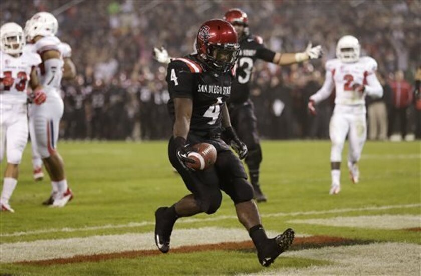 San Diego State running back Adam Muema (4) runs it in for a touchdown against Fresno State during the first half in an NCAA college football game Saturday, Oct. 26, 2013, in San Diego. (AP Photo/Gregory Bull)