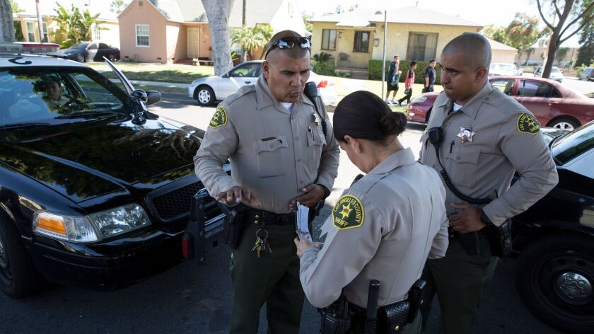 Sheriff's deputy Marino Gonzalez, left, talks with deputies while investigating a disturbance in May