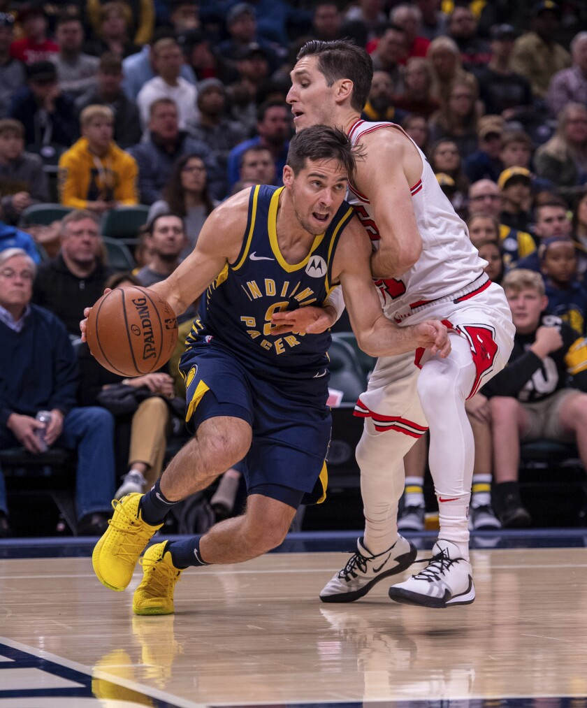 Indiana Pacers guard T.J. McConnell (9) drives the ball along the baseline as he is defended by Chicago Bulls guard Ryan Arcidiacono, right, during the first half of an NBA basketball game in Indianapolis, Sunday, Nov. 3, 2019. (AP Photo/Doug McSchooler)