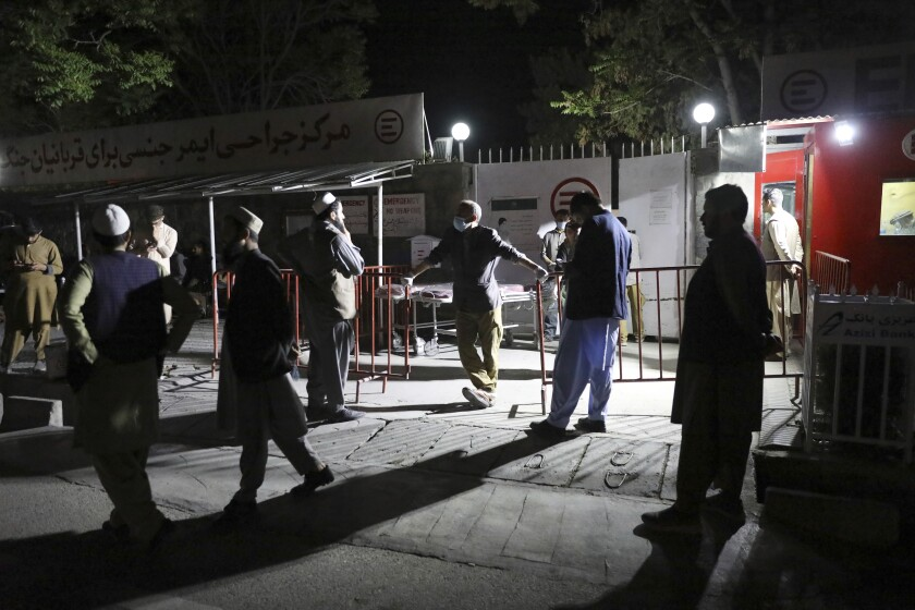 Afghans wait outside the hospital to see their relatives in Kabul, Afghanistan