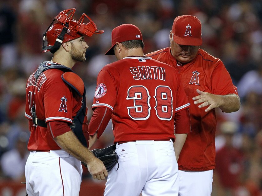 Los Angeles Angels manager Mike Scioscia, right, removes relief pitcher Joe Smith (38) with catcher Chris Iannetta also at the mound during the eighth inning of a baseball game against the Texas Rangers in Anaheim, Calif., Saturday, July 25, 2015. (AP Photo/Alex Gallardo)