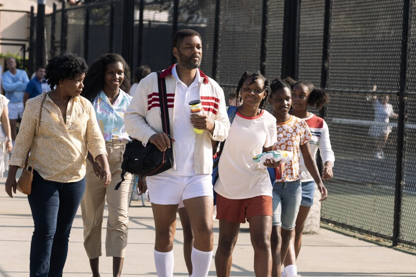 Will Smith in tennis gear walks with a group of women and girls at a tennis complex