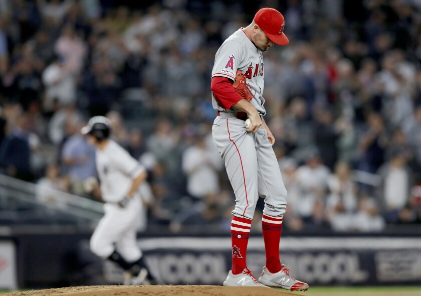 Angels pitcher Andrew Heaney reacts as New York Yankees' DJ LeMahieu rounds third base after his three-run home run in the second inning on Thursday in New York.
