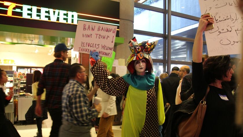 Artist Rachel Mason, dressed as her character FutureClown, stands among protestors at the arrivals gate at Tom Bradley International Airport.