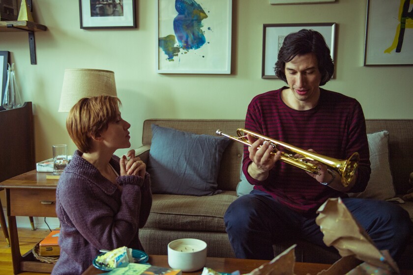 "Scarlett Johansson, kneeling, and Adam Driver, holding a trombone on a couch, in ""Marriage Story."""