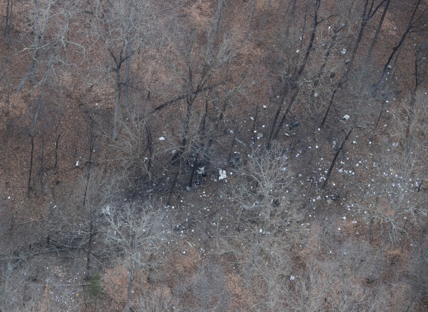 Rescue workers sort through the wreckage of a small plane in a wooded area near Memphis, Ind., Frida