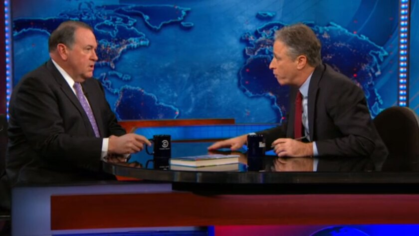 """Mike Huckabee, left, and Jon Stewart disagree on """"The Daily Show."""""""