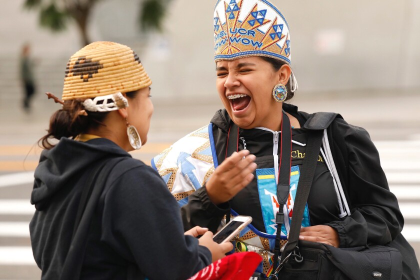 Katianna Warren, right, laughs with Miztlayolxochitl Aguilera at festivities kicking off Indigenous People Day in 2018.