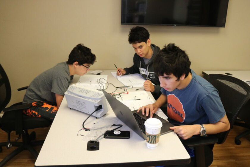 EE Level-1 students (Peter Fregoso, Arman Aryan and Shiva Malhotra) are working with an oscilloscope and function generator to test their circuit.