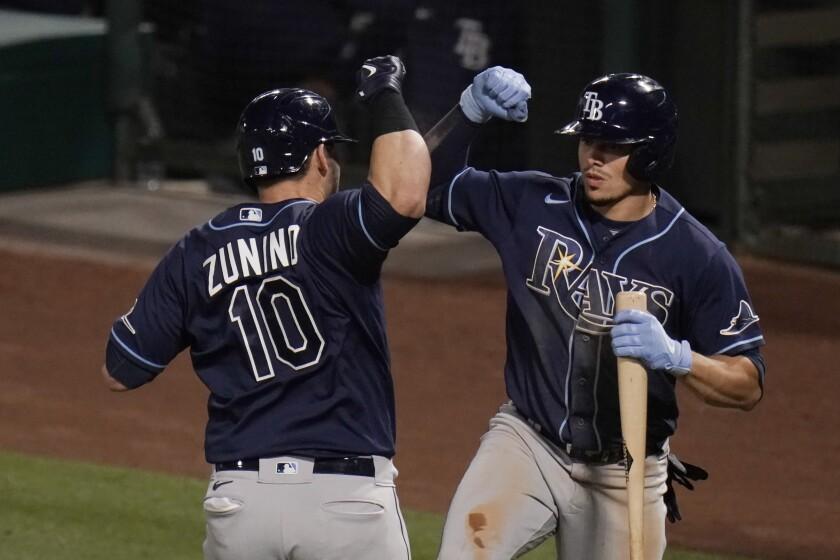 Mike Zunino (izquierda), de los Rays de Tampa Bay, celebra un jonrón con su compañero Willy Adames en el séptimo inning del juego de la MLB que enfrentó a su equipo con los Angelinos de Los Ángeles, el 6 de mayo de 2021, en Anaheim, California. (AP Foto/Jae C. Hong)