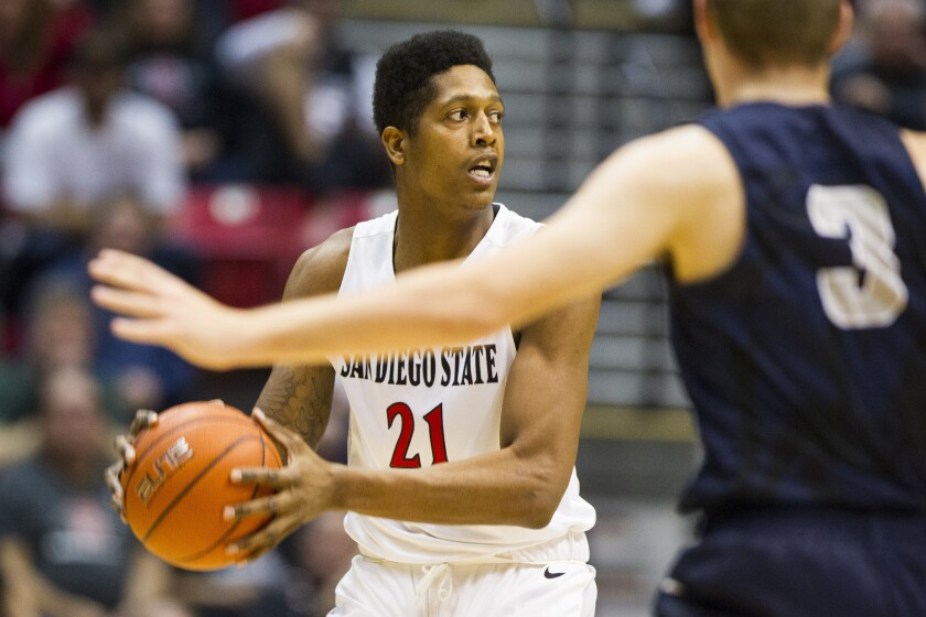 SDSU forward Malik Pope looks to pass as he is covered by Utah State guard Sam Merrill.