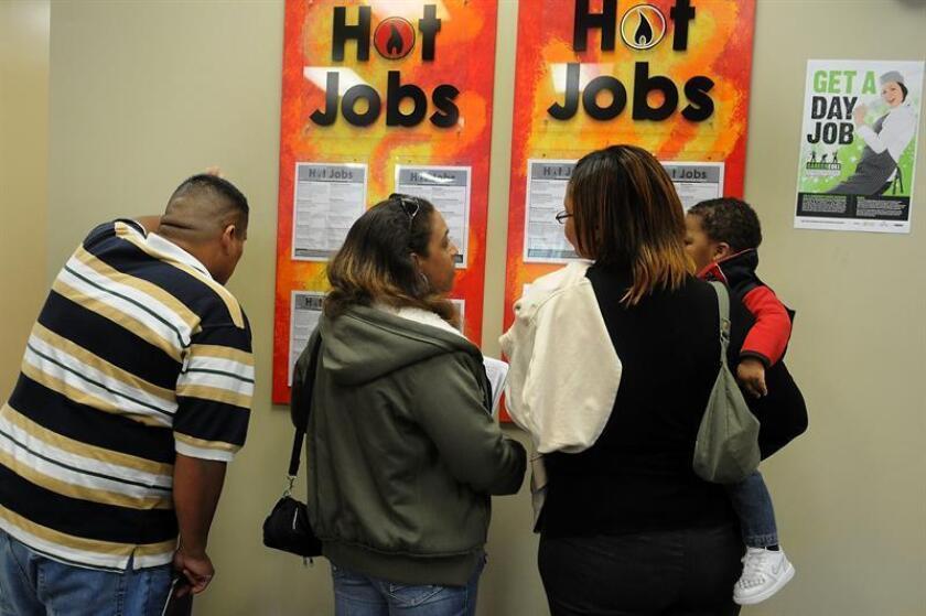 """Personas en busca de trabajo revisan anuncios de empleo colocados en la sala de espera de la oficina de empleo """"Work Force"""" de la Florida central en la ciudad de Orlando (norte de Florida). EFE/Archivo"""