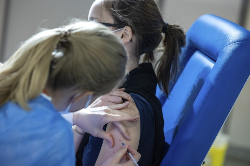 A healthcare worker administers a dose of the AstraZeneca COVID-19 vaccine to a woman at the Brussels Expo center in Brussels, Thursday, March 4, 2021. The Expo is one of the largest vaccination centers in Belgium. (AP Photo/Olivier Matthys)
