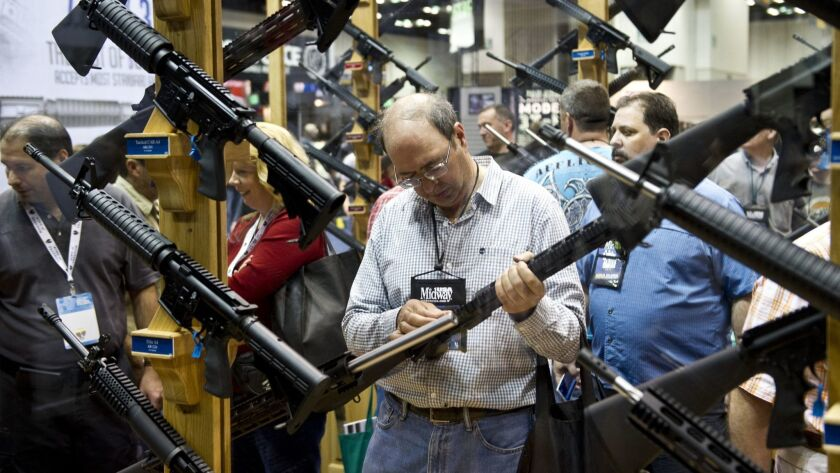 A man examines a weapon at the National Rifle Assn.'s annual meeting in Indianapolis in 2014. A new study finds that gun injuries drop 20% while the NRA is holding its convention.