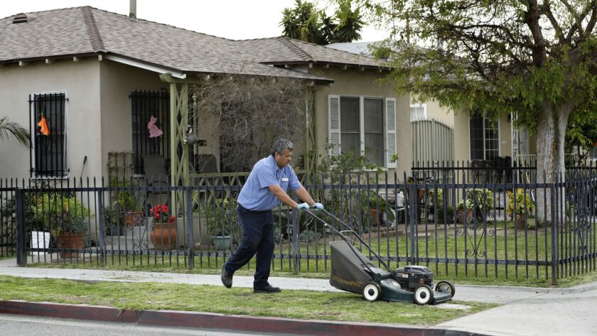 BOYLE HEIGHTS, CA-MARCH 19, 2018: Francisco Cruz mows the parkway in front of his home on 53rd St.