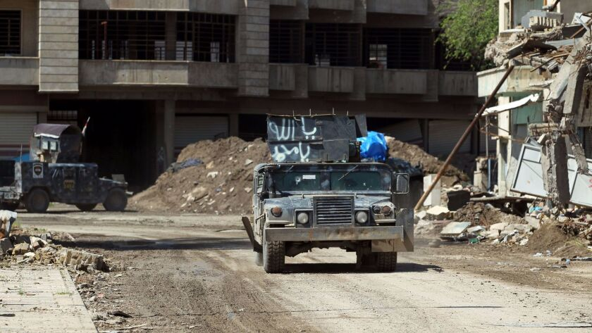 Iraqi forces drive down a street in the old city of Mosul on April 15, 2017.