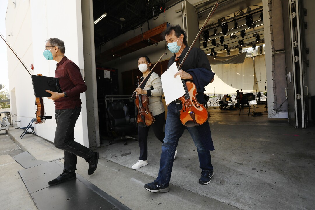 Musicians walk out of the backstage area